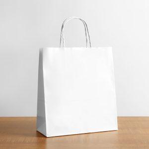 Paper bag on table against white background. Mockup for design