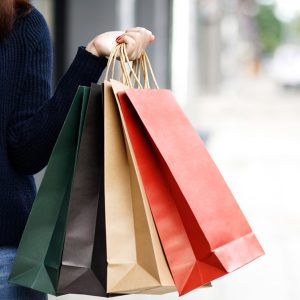 Closeup of woman hand holding shopping bag colorful paper on the