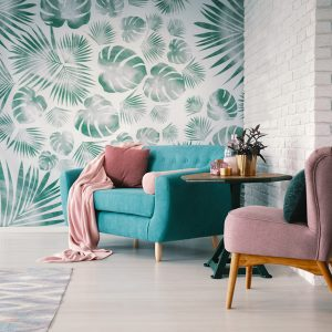 Chair and turquoise sofa in green living room interior with leav